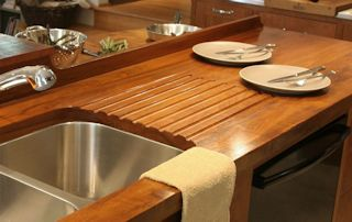 Teak face grain countertop including an integrated sloping drainboard for an undermount sink.