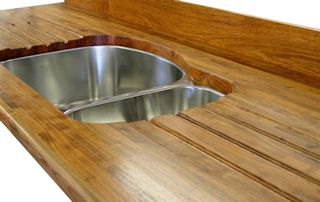 Mesquite edge grain countertop with an integrated sloping drainboard for an undermount sink.