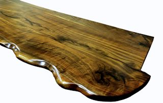 One section of a multi-section walnut slab bar top.  sculpted wane edge and waterlox semi-gloss finish.