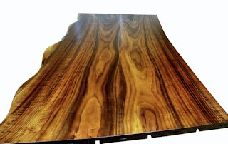 One section of a multi-section walnut slab bar top.  Using book-matched slabs with a sculpted wane edge and waterlox semi-gloss finish.