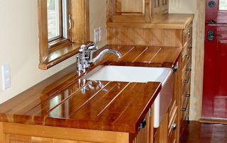 Cherry face grain countertop with an integrated sloping drainboard on each side of a farm sink.