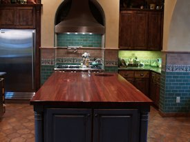Jatoba edge grain custom wood island countertop with hand carved trash cover.