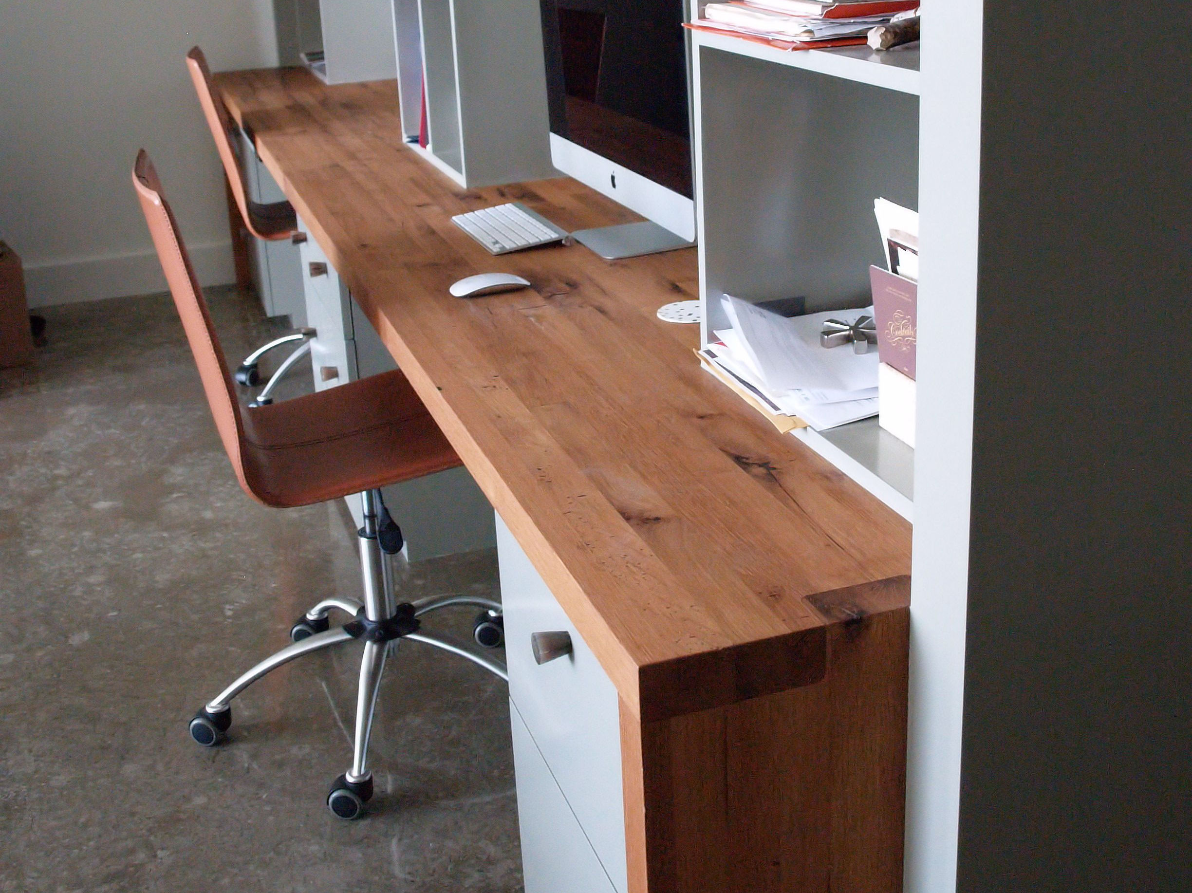 Reclaimed White Oak custom wood desk with DeVos Puzzle Joint along the length.  Finger Joint ends with Waterfall return to the floor and Tung-Oil finish.