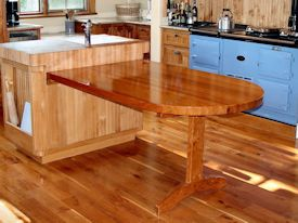 Custom cherry trestle style penninsula table with hard maple accents.